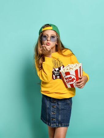Young charming teenage girl in a yellow hoodie and denim mini skirt holds a bucket of popcorn on a green background. sends a kiss Stock Photo