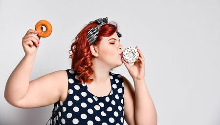 Portrait of beautiful cheerful fat plus size woman pin-up wearing a polka-dot dress isolated over light background, eating and kissing a donut.