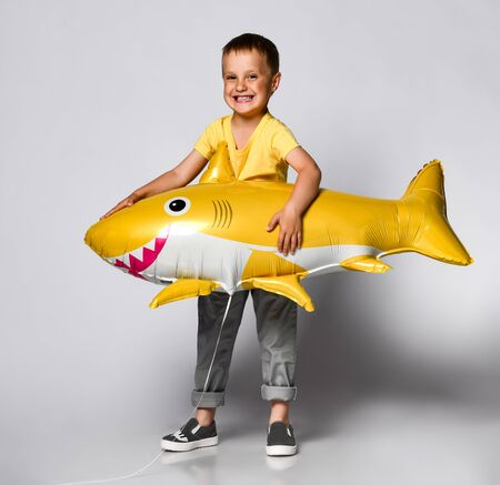 little boy, dressed in festive clothes, wears a balloon in the shape of a yellow shark fish, celebrates a holiday, has a wide smile, stands on a light background, being in a good mood. Children and holiday concept