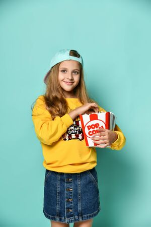 Young charming teenage girl in a yellow hoodie and denim mini skirt holds a bucket of popcorn on a green background Imagens