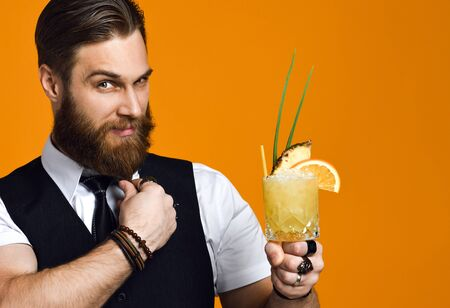 Stylish bearded male with a mustache has stylish hair, holding a cocktail and looks into the frame, in a black vest on a yellow studio background