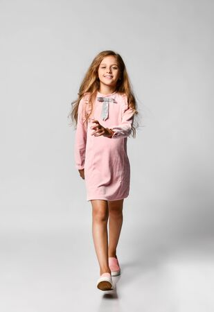 beautiful little girl with long blond hair and blue eyes in a casual pink dress and gym shoes runs to meet you. teenager style. Sale, holidays, birthday concept.