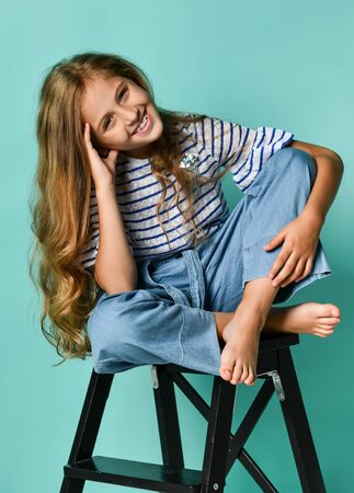 Stylish little girl child wearing summer or autumn jeans clothes sitting on a high chair in the studio. Fashionable kid.