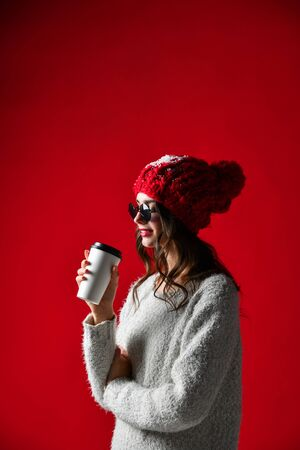 Portrait of Hipster stylish woman in knitted red hat hold drink takeaway hot coffee over red wall