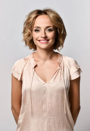 Headshot portrait of a happy blonde girl in beige blouse smiling looking at camera. White background. Positive human emotions Imagens