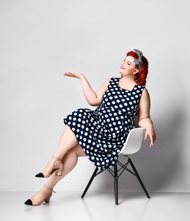 cute young plus-sized girl wearing a polka-dot dress and American-style hair band. She sits on a chair and shows to the side. Advertising. Imagens