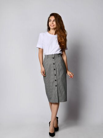 Young beautiful woman posing in a new white blueska and gray skirt with buttons, on the high heels of the whole body on a white background