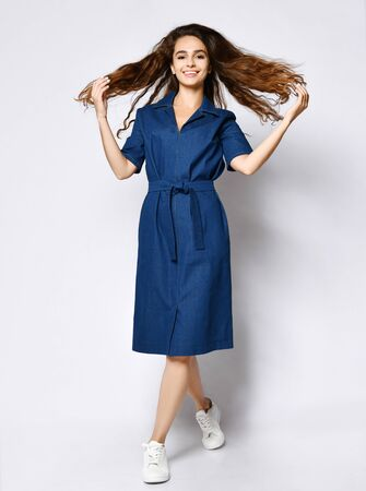 Female model in a blue urban classic dress shirt and full-length gym shoes. A cute girl in romantic clothes with long developing hair goes to the camera.