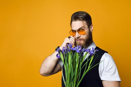 brutal bearded young man in yellow stylish glasses and waistcoat holds a bouquet of irises flowers on a yellow studio background.