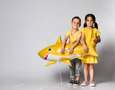 Positive little children, dressed in festive clothes, wears a balloon in the shape of a yellow shark fish, celebrates a holiday, has a wide smile, stands on a light background, being in a good mood. Children and holiday concept