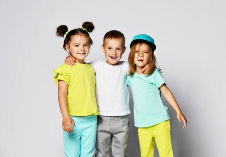 Studio portrait of children on a light background: full body shot of three children in bright clothes, two girls and one boy. Triplets, brother and sisters. laughing and screaming loud have fun in the studio