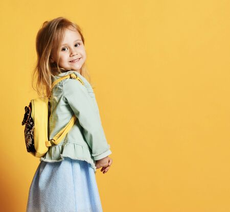 Pretty little girl child in stylish dress and jeans with a yellow backpack behind her back jumping smiling looking at the camera. on yellow studio background Imagens
