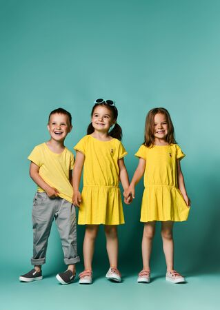portrait of children on a green background: full body shot of three children in bright clothes, two girls and one boy. Triplets, brother and sisters. laughing and screaming loud have fun in the studio