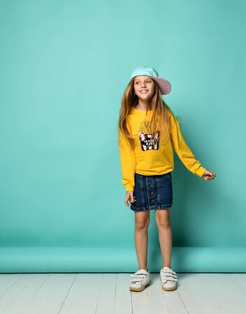 positive young female wearing orange hoody and baseball cap posing on a blue background Imagens