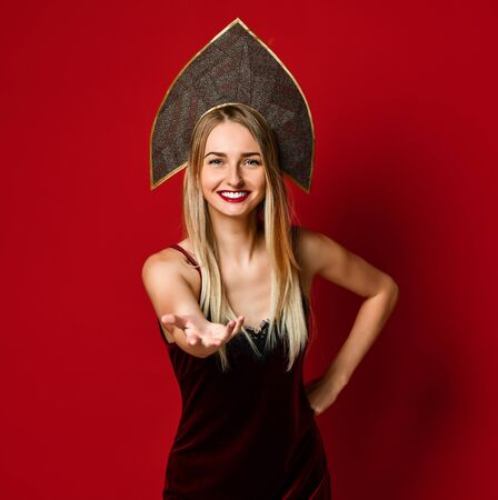 Attractive blonde woman in cap kokoshnik raised up palm arm hand at you, isolated over red background. concept of free female welcoming