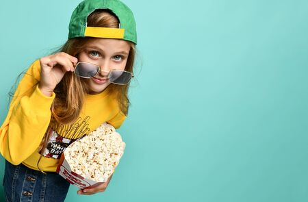 Young charming teenage girl in a yellow hoodie and denim mini skirt holds a bucket of popcorn on a green background. Looks over your sunglasses. Imagens