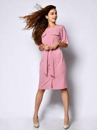 Junges Mädchen in einem Business-Kleid, das Kleidung trägt, ziemlich lächelnd auf weißem Hintergrund. Ein schlankes weibliches Model in einem rosafarbenen Businesskleid und weißen Stilettos schaut lächelnd in die Kamera.