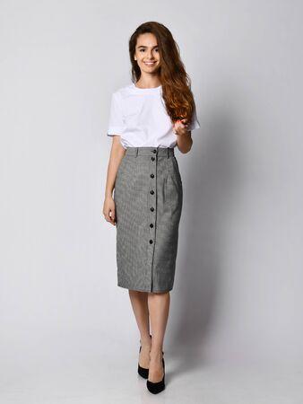 Mujer hermosa joven posando en un nuevo blueska blanco y falda gris con botones, en los tacones de todo el cuerpo sobre un fondo blanco. Foto de archivo
