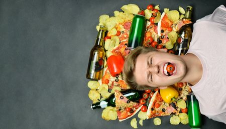 young man lies surrounded by pieces of pizza. chips bottles with alcohol and beer. Morning after meeting with friends and drinking. Guy holds teeth tomato. copy space