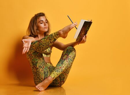 Portrait of beautiful young fitness woman in sportswear doing yoga, stretching her leg, reading a book on studio backdrop yellow background. athletic girl exercise, training, workout, stretching, relaxation, healthy lifestyle.