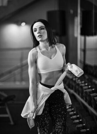 Athletic girl is standing after training in the gym near the mirror, knotting a sports jacket on the hips. black and white photography