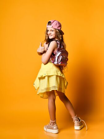 Full-length indoor portrait of a teenager girl in a yellow skirt. sneakers and a cap with a glamorous backpack. It is half a turn to the camera, on a yellow background. fooling around in the studio.