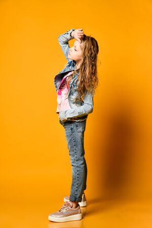 Young teen girl model posing on a yellow background in jeans and a jacket. with long hair gathered in a high tail Imagens