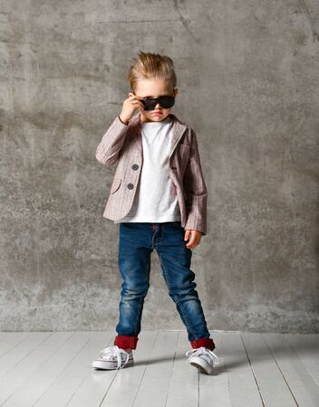 little boy fashionista in light jeans and a stylish jacket, looking over his glasses against the background of a concrete wall. Stylish childhood