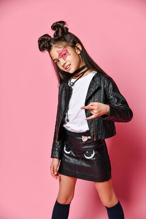 Portrait of a little hipster girl in a bomber jacket and miniskirt, showing a yo sign with fingers, fashionable childhood. on pink wall studio