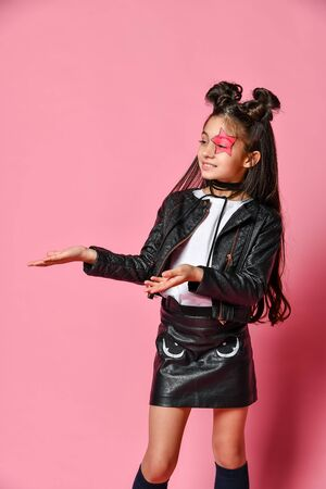 Little - fashionable hipster punk girl - dressed in a leather jacket and skirt, black knee-highs and a white T-shirt, with a funny hairstyle and a makeup star on the face, points to the side. Imagens
