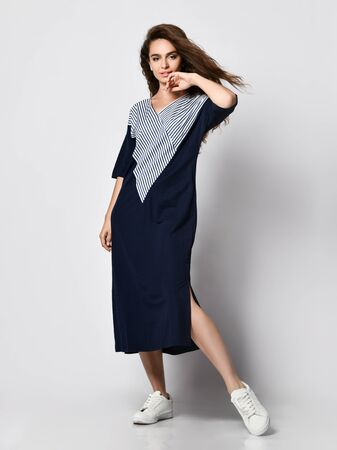 Fashionable woman with long hair in a beautiful long blue dress with a light insert, sneakers. Fashion spring summer autumn photo