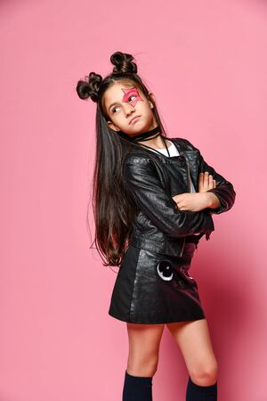 hipster punk girl - dressed in a leather jacket and skirt, with a funny hairstyle and a makeup painted star on her face, folded her arms across her chest and looks behind her. Standard-Bild