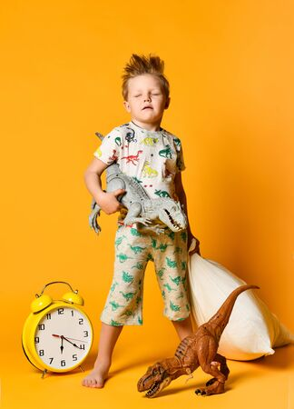 Little boy of preschool age with a pillow in his hands and a toy dinosaur waking up on an alarm clock. Photo in studio on a yellow background.