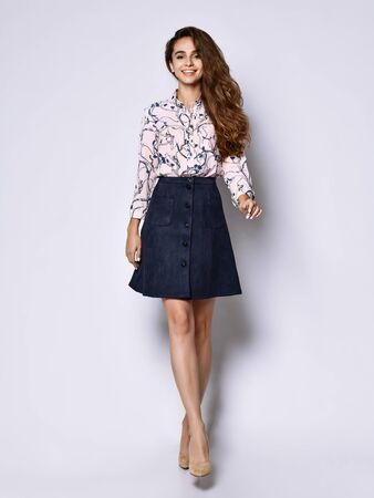 Vertical of a short beautiful cheerful young woman posing in solitude, in a light silk blouse with floral patterns, a dark short skirt with buttons and high-heeled shoes, looking with a smile