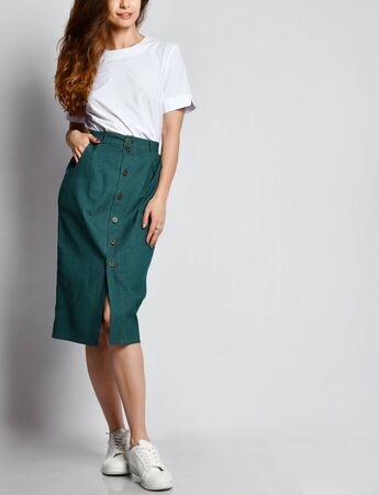 Cropped photo of a young brunette girl with long hair in a white blouse and green skirt. on a light background.