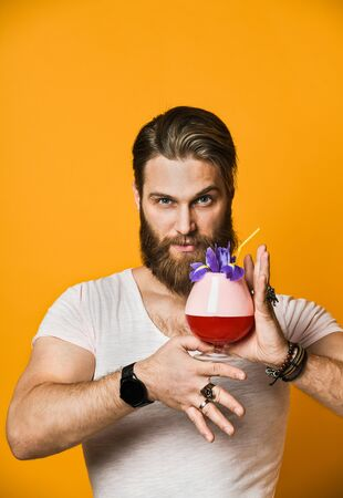 Attractive, stunning and cheerful bearded young man holding a multicolored cocktail with a straw and looking at the camera. On a yellow background. Imagens