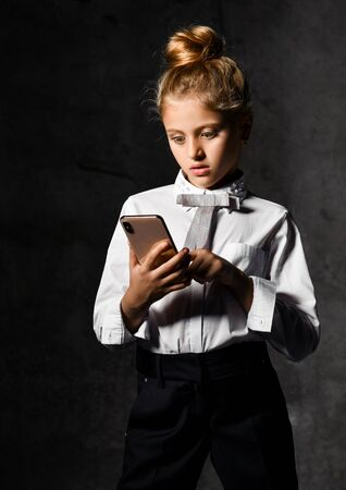 Portrait of a small schoolgirl standing in uniform, dark trousers and a light blouse looking at her smartphone. Imagens