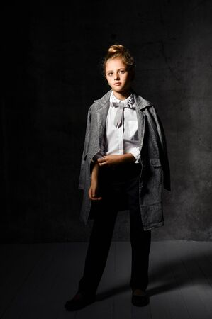 Fashion shot in the studio. Professional model, fashion clothes and style, Young girl in a white blouse and dark breeches with a gray cloak.