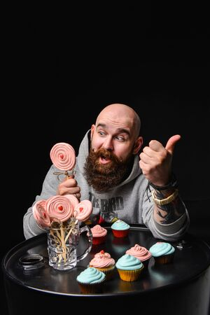 A happy bearded bald man is holding a lollipop cake and some more on the table. The guy tastes the cake and enjoys.