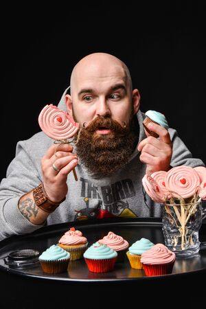 Happy bearded bald man holding two cream cakes on black background. A man squints between two sweets