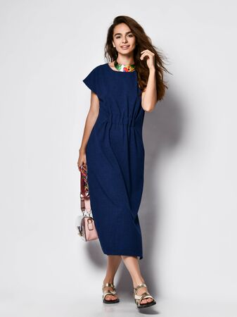 Slender curly female model in a blue urban long dress in full growth. Lovely girl in romantic clothes goes on a date, to the office, to a meeting. Urban fashion.