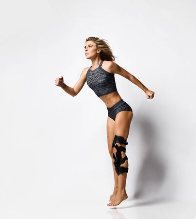 Beautiful young athletic woman with a knee bandage playing sports gymnastics yoga, recovery after injury. Isolated