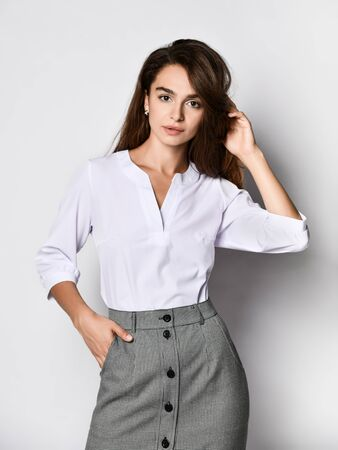 Young beautiful woman office manager posing in a new casual white blouse and classic straight dark skirt on a light background