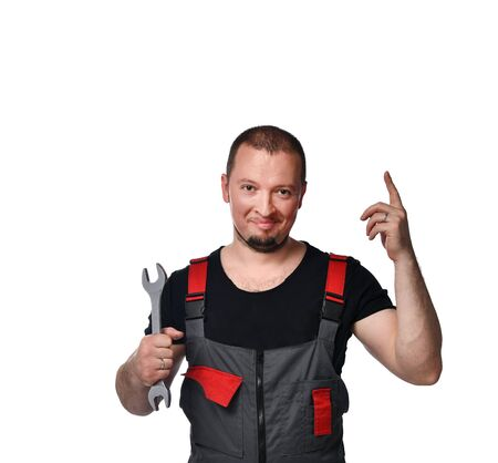 Smiling auto mechanic with wrench standing hands folded on white background Banco de Imagens