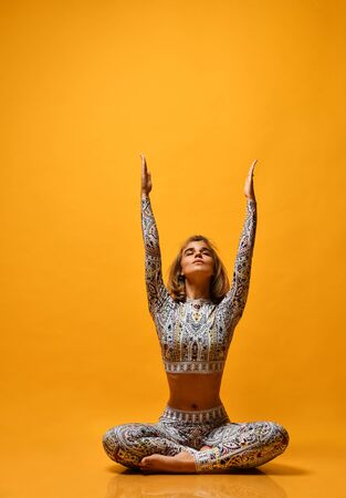 Portrait of a beautiful young woman with floral print sport costume working out against a yellow wall, doing yoga or pilates training, sitting in a baddha konasana, bound corner, hands raised up. Full shot