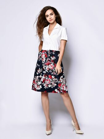 beautiful cheerful young woman posing in solitude, in an official light blouse, a light skirt with a floral print and high-heeled shoes looking to the side with a smile Stock Photo
