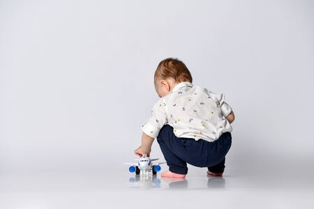 little toddler boy sits on a light wall background in an empty room with a toy airplane Stock Photo