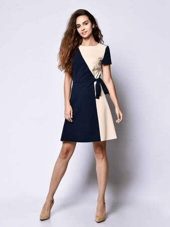 Luxurious curly female model in a two-tone dress and a full-length stilettos. Lovely girl in romantic clothes goes on a date, to the office, to a meeting. Фото со стока