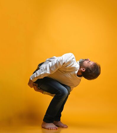 bearded man practicing yoga doing stretching exercises dressed casually in shirt and jeans, Performs asana posture chair. Utkatasana., against orange background
