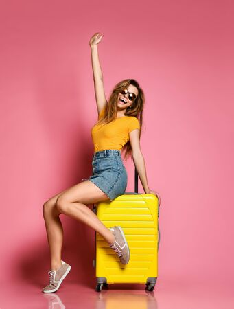 Traveler tourist woman in summer casual clothes with travel suitcase isolated on pink background. Travel concept.